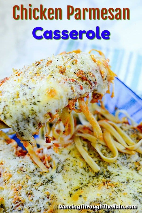 Chicken parmesan casserole in a blue dish with a cheesy piece being lifted by a spatula