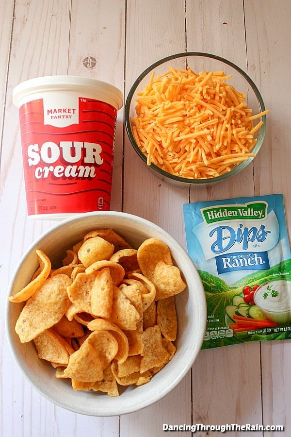Sour cream, shredded cheese, Fritos in a bowl and Ranch dip packet