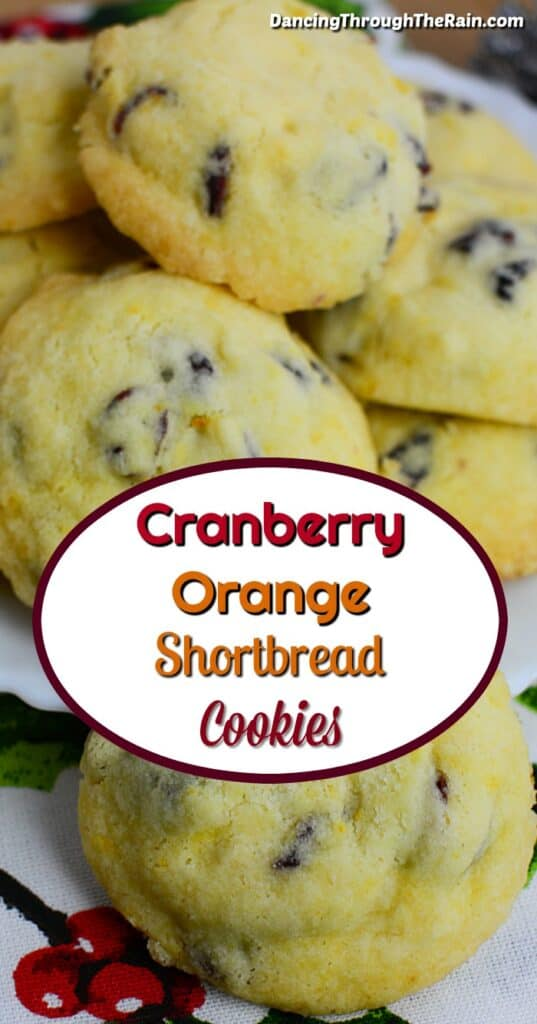 Cranberry Orange Shortbread Cookies in a stack on a white berry tablecloth
