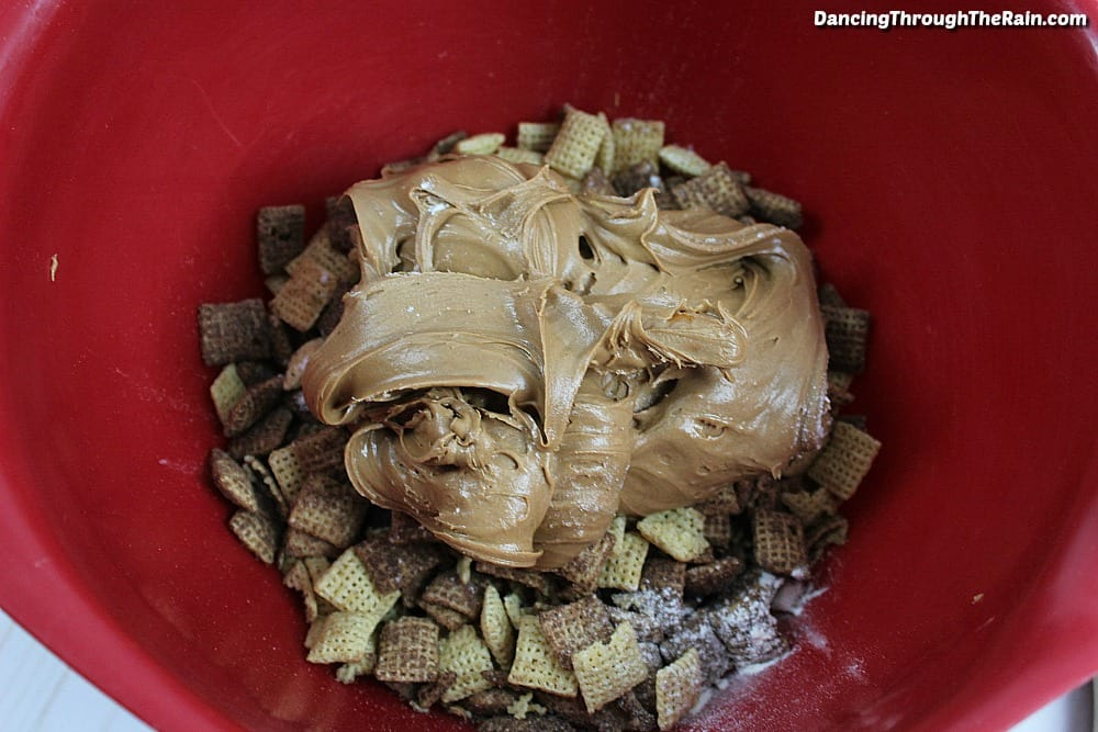 Chocolate Chex Mix with peanut butter and Nutella on top in a red mixing bowl