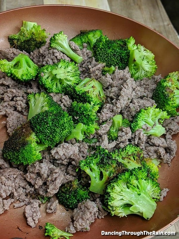 Beef and broccoli in a pan cooking