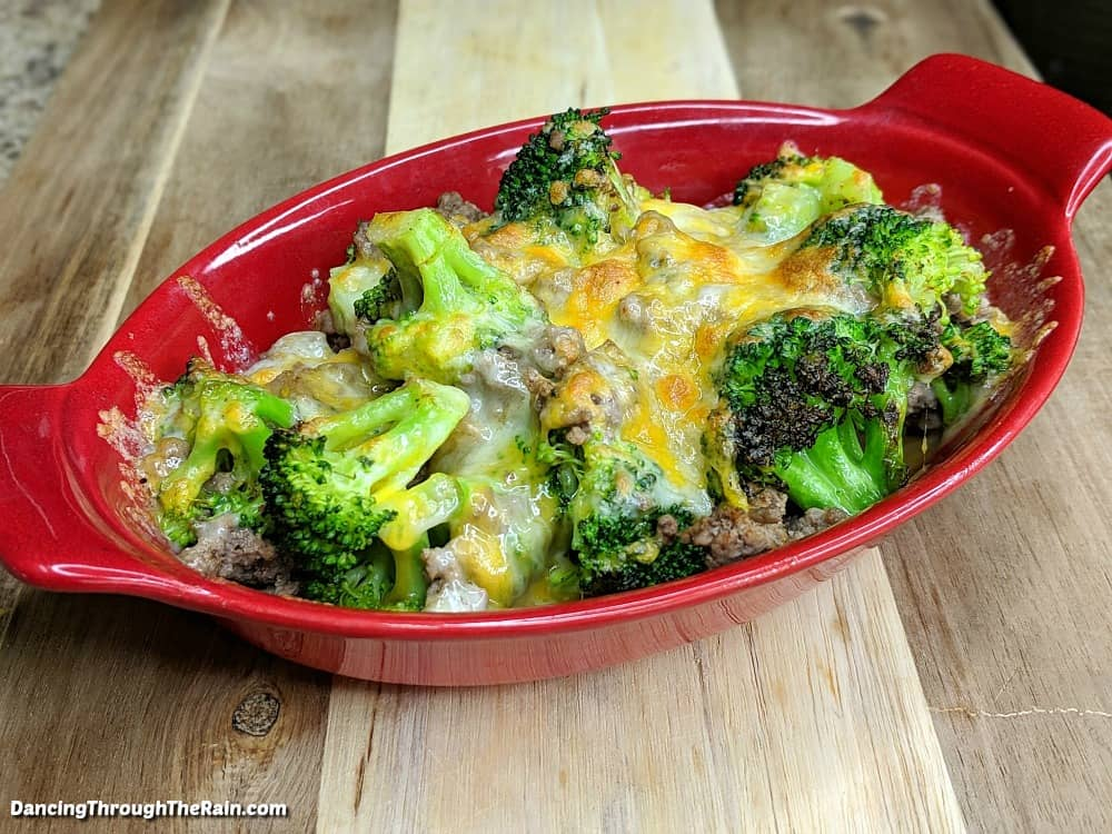 Beef broccoli cheese casserole in a red casserole dish on a wooden table