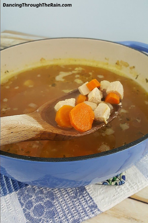 Classic Chicken Soup in a blue dutch oven with a wooden spoon