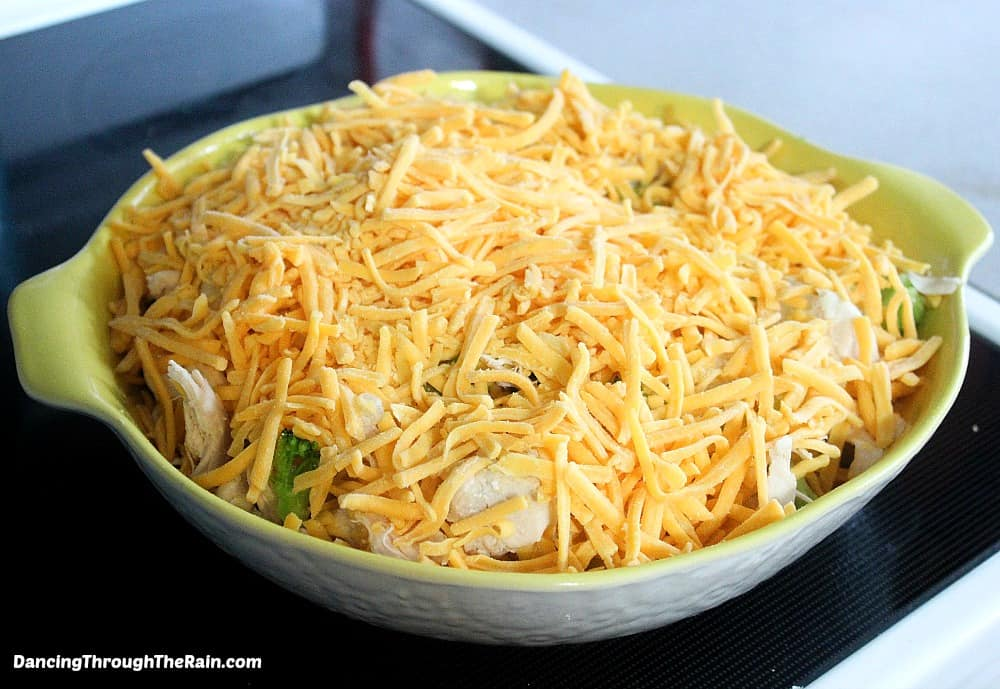 Yellow baking dish with riced cauliflower, broccoli, shredded chicken and shredded cheese