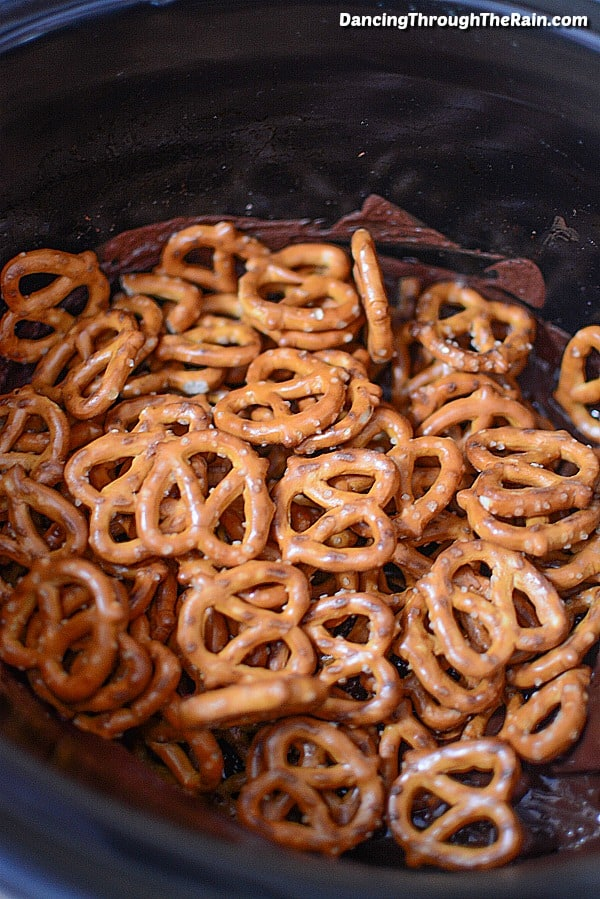 Pretzels in a slow cooker with melted chocolate underneath