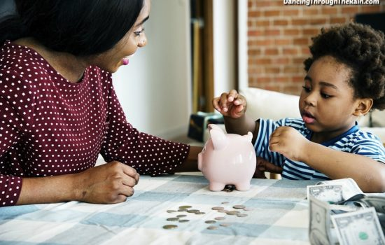 A mom showing her son how to put coins in a piggy bank