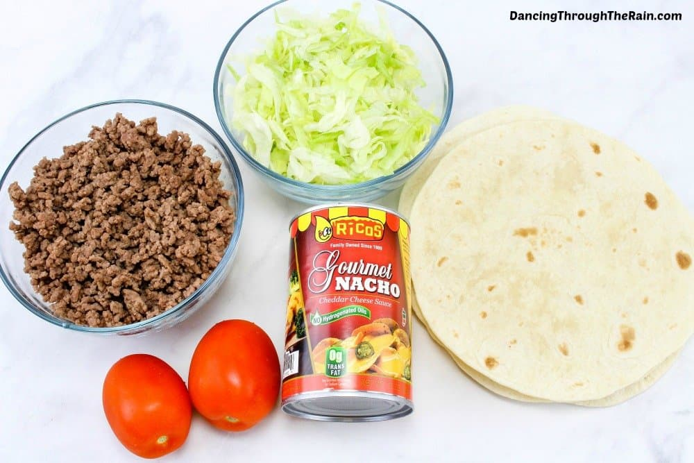 Ground beef, tomatoes, lettuce, nacho cheese and tortillas on a cutting board
