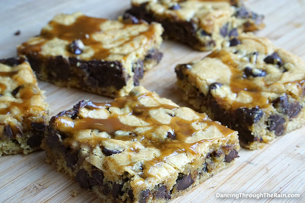 Five Chocolate Chip Caramel Cookie Bars on a wooden table
