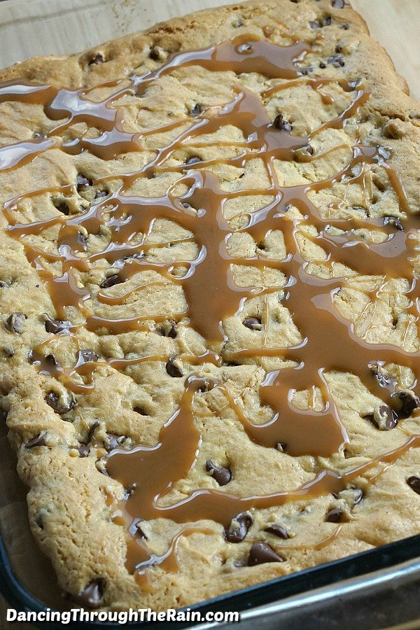 Baked Chocolate Chip Caramel Cookie Bars with caramel drizzle on top