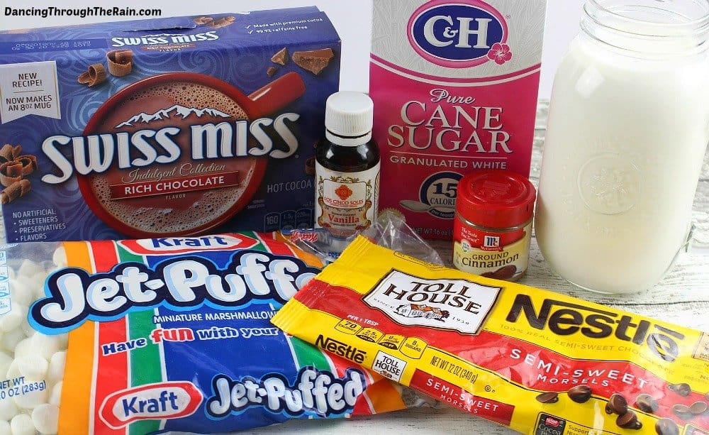 Ingredients for Homemade Chocolate Pops: A box of Swiss Miss, a pink box of sugar, a bag of Jet-Puffed marshmallows, Nestle Toll House chips and a jar of milk on a white wooden table