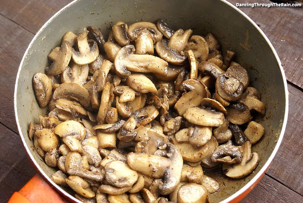 Cooked mushrooms and butter in a pan