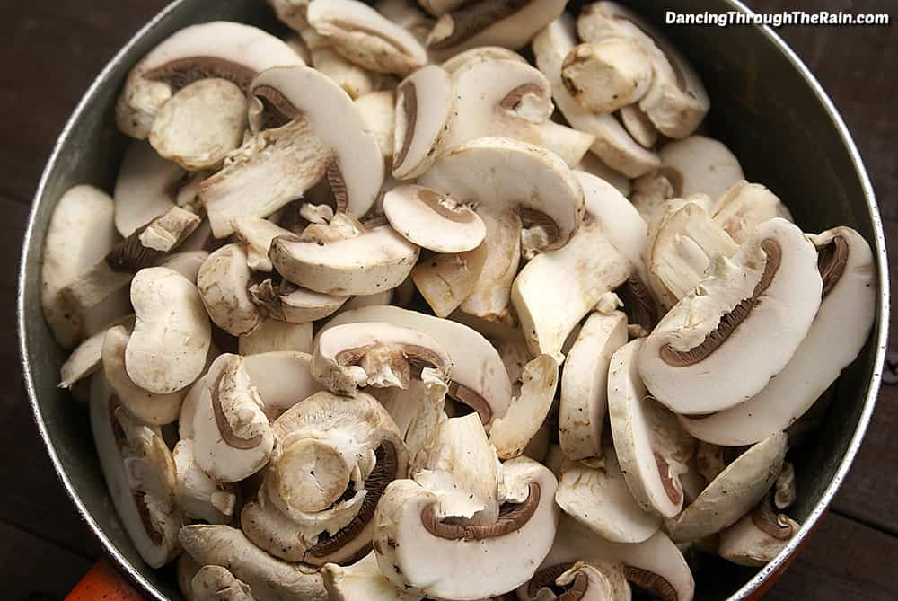 Sliced raw mushrooms in a pan with butter