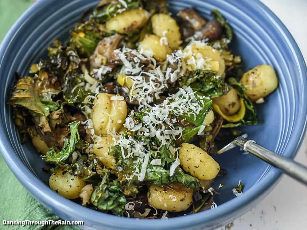 Gnocchi with leeks, kale, and mushrooms in a blue bowl