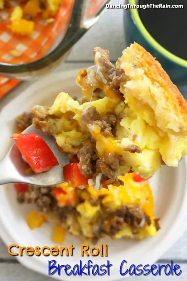 A square of Crescent Roll Breakfast Casserole on a white plate being scooped up on a fork