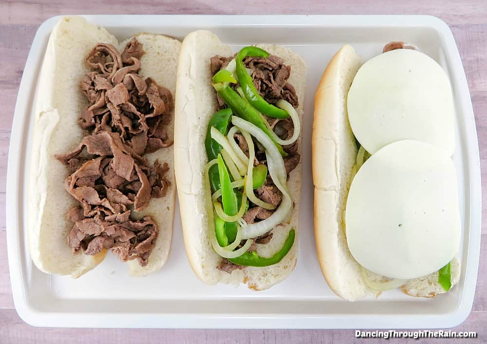 Three Philly Cheesesteaks being assembled
