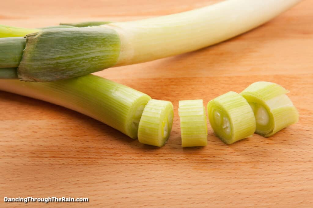 Two leeks on a wooden cutting board with four pieces chopped into circles