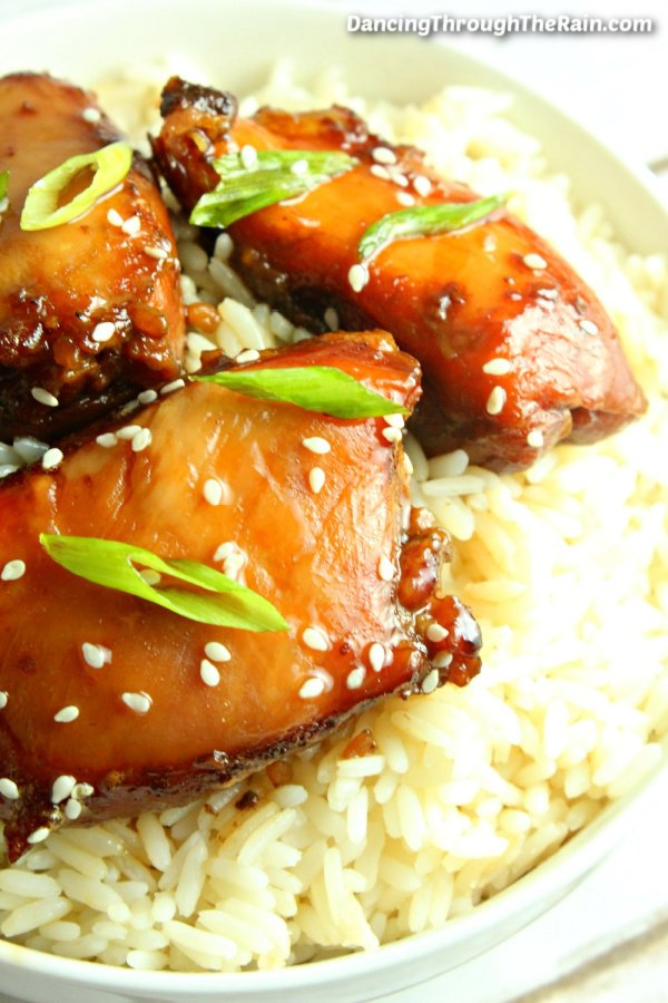 Three pieces of Easy Slow Cooker Mongolian Chicken on a bed of white rice in a white bowl
