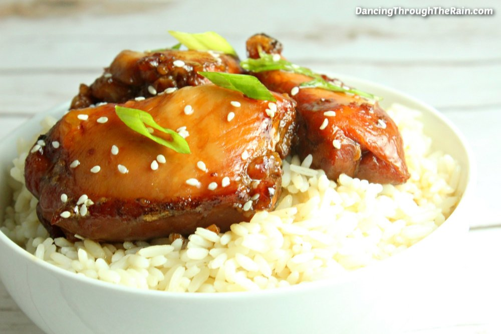 Three pieces of Slow Cooker Mongolian Chicken on a bed of white rice in a white bowl on a white table