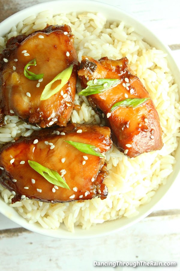 Three Slow Cooker Mongolian Chicken pieces on a bed of rice on a table