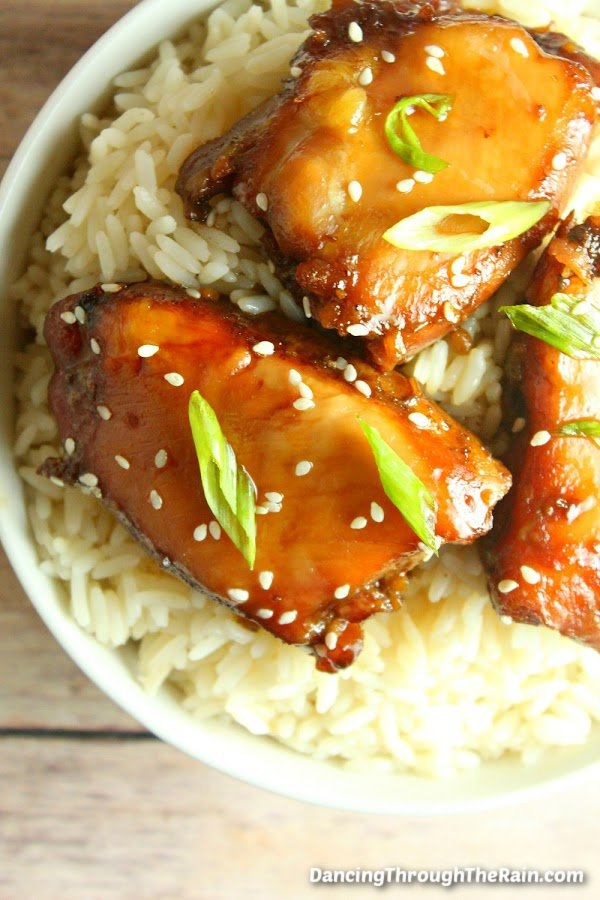 Three Slow Cooker Mongolian Chicken pieces on white rice on a table