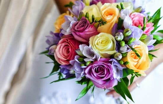 A colorful wedding bouquet being held by a bride