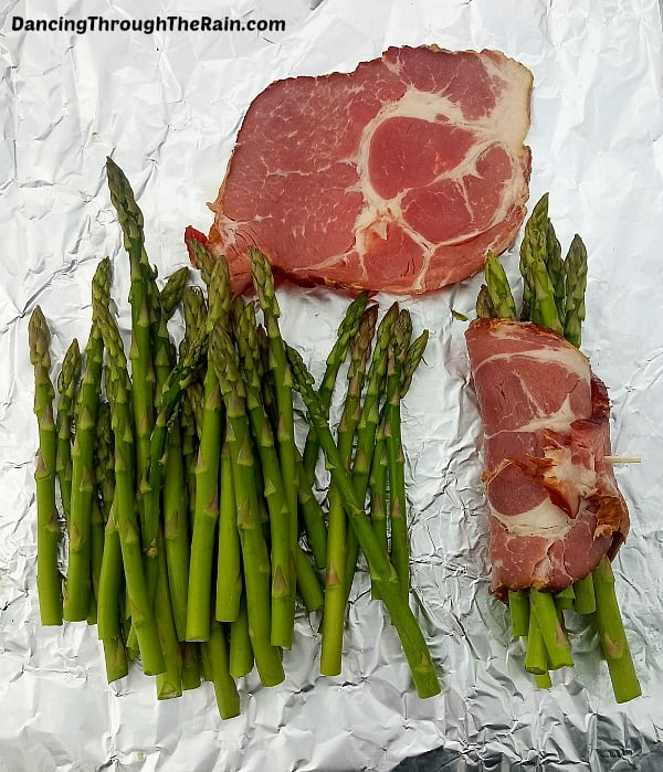 Bacon slices with asparagus being wrapped