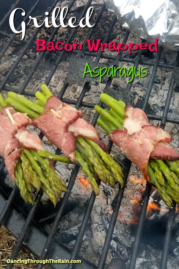 Three bunches of bacon wrapped asparagus on the grill grates over a fire