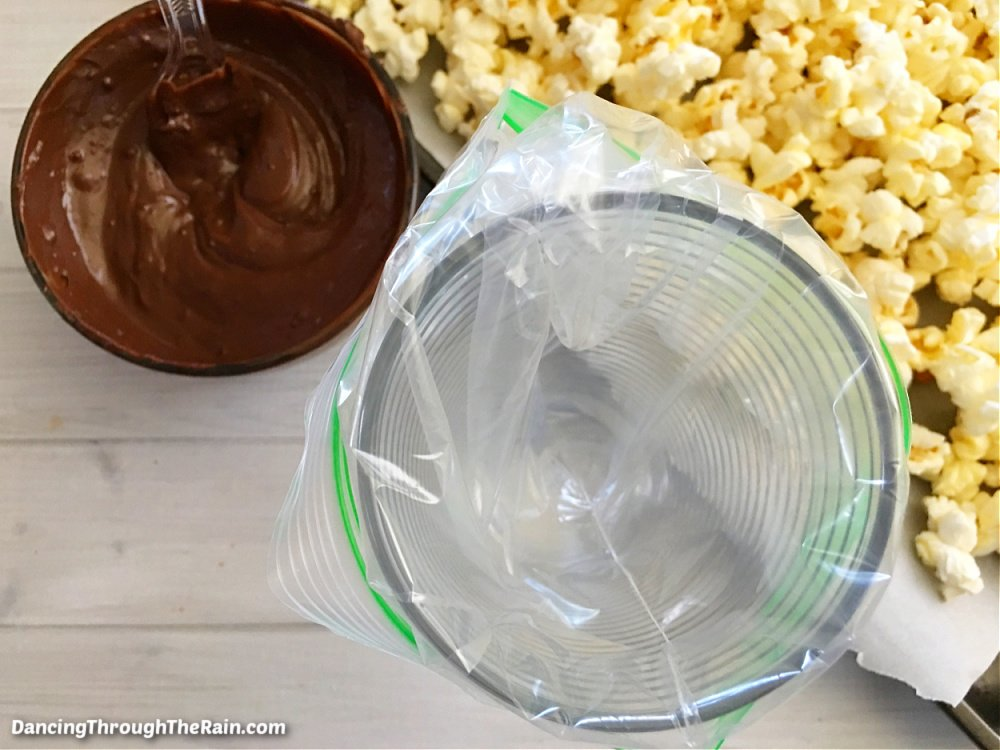 A clear bowl of melted chocolate next to a clear glass with a pastry bag inside next to a baking sheet of popped popcorn