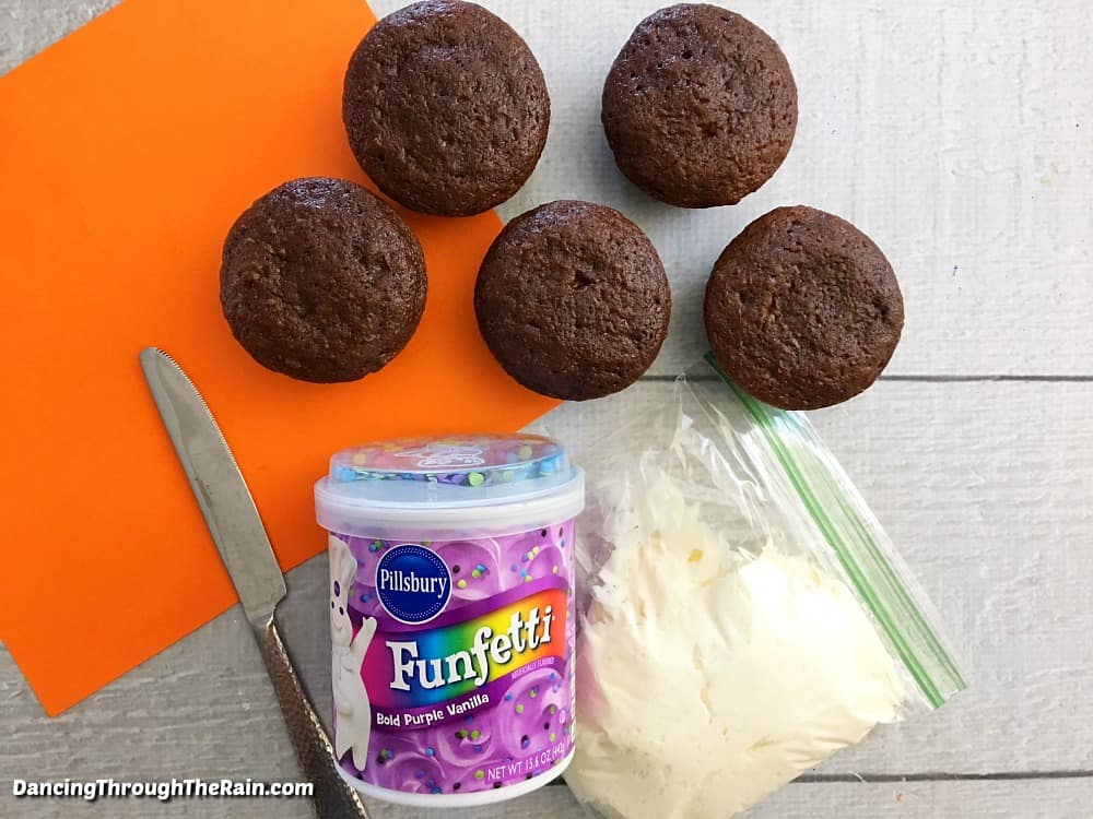 Baked chocolate cupcakes next to a tub of purple frosting on an orange cutting board and a metal knife