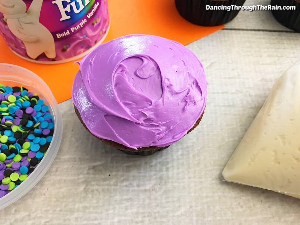 Chocolate cupcake frosted with purple frosting on a table next to the tub of frosting, a clear bowl of multicolored sprinkles and a piping bag of white frosting