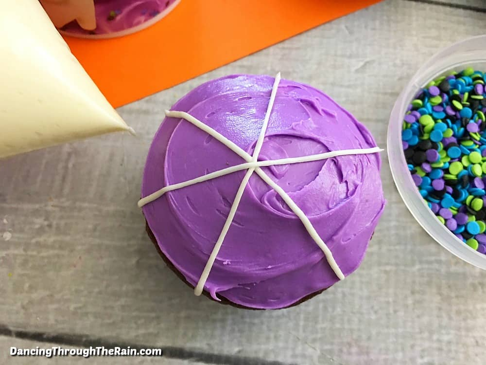 Chocolate cupcake with purple frosting and three white lines across like a star