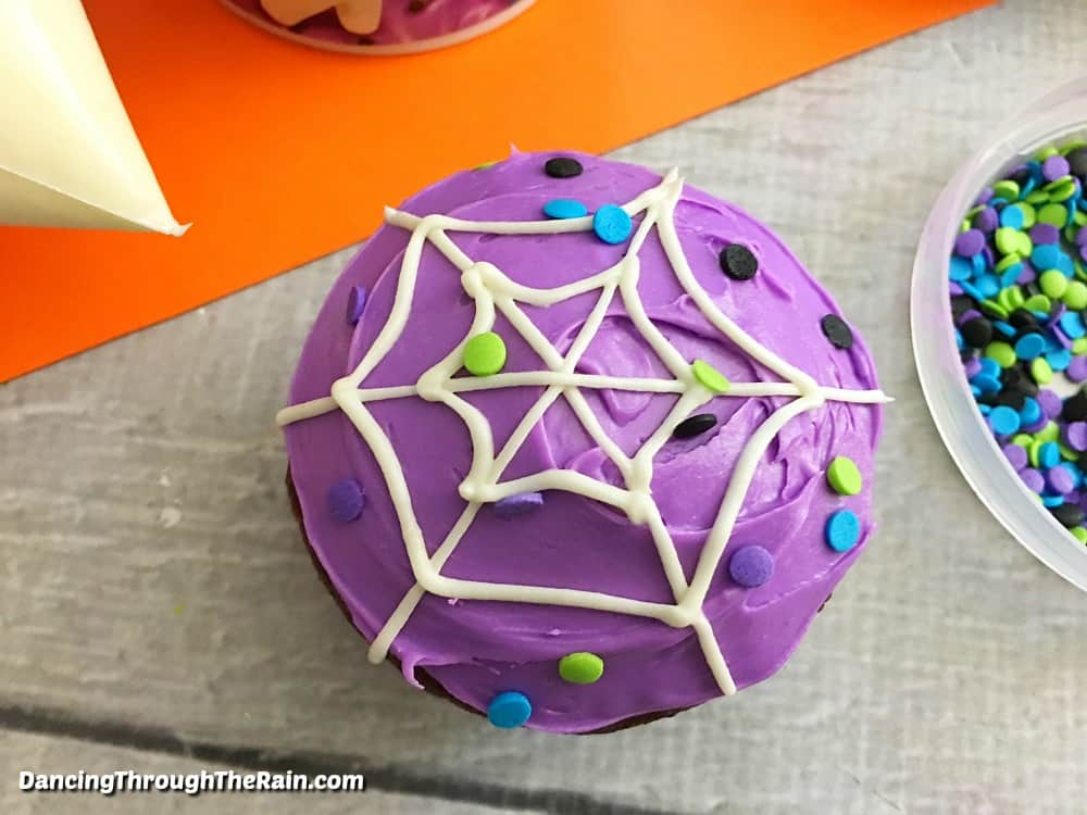 Spiderweb cupcakes surrounded by ingredients