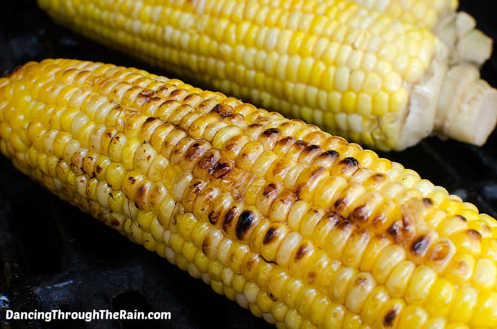 Two Sweet and Spicy Grilled Corn on the Cob on a black grill