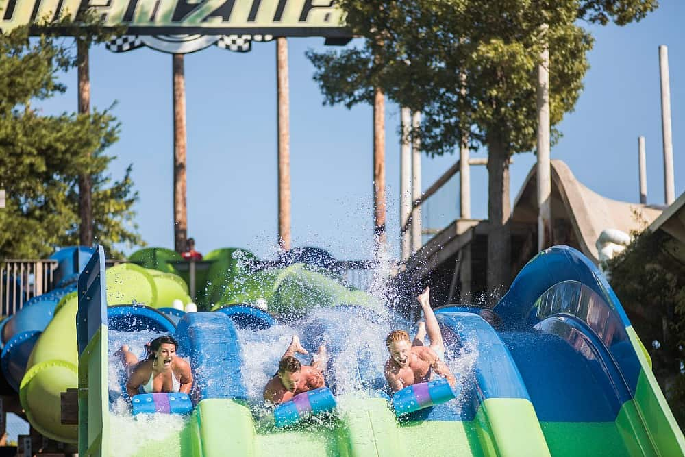 Three people on waterslides starting to race each other