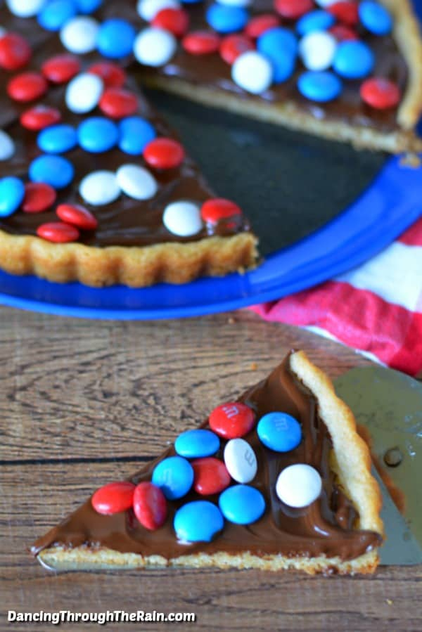 Red White And Blue M&M Cookie Tart sliced and being held on a spatula