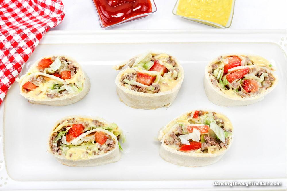 Five Cheeseburger Pinwheels on a white rectangular plate next to small bowls of ketchup and mustard
