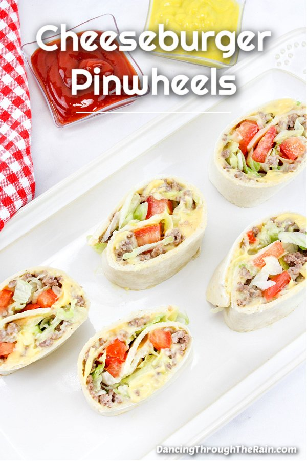 Five Cheeseburger Pinwheels on a white rectangular plate next to a red and white checkered napkin and small bowls of ketchup and mustard