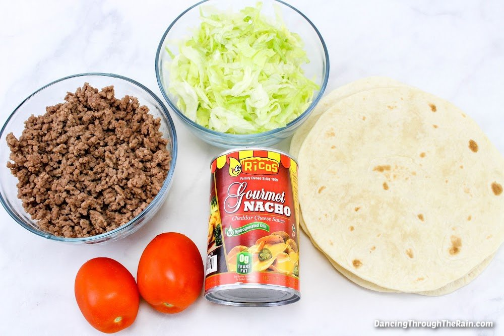 A clear bowl of cooked ground beef, another of lettuce shreds, two Roma tomatoes, a can of nacho cheese and a stack of flour tortillas