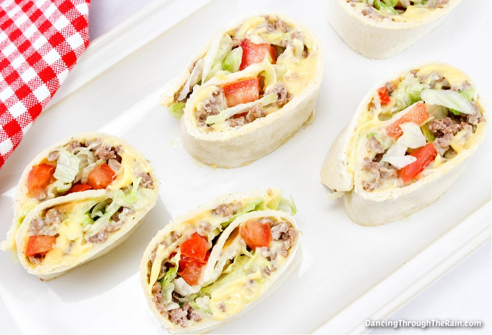 Five Cheeseburger Pinwheels on a white rectangular plate next to a red and white checkered napkin