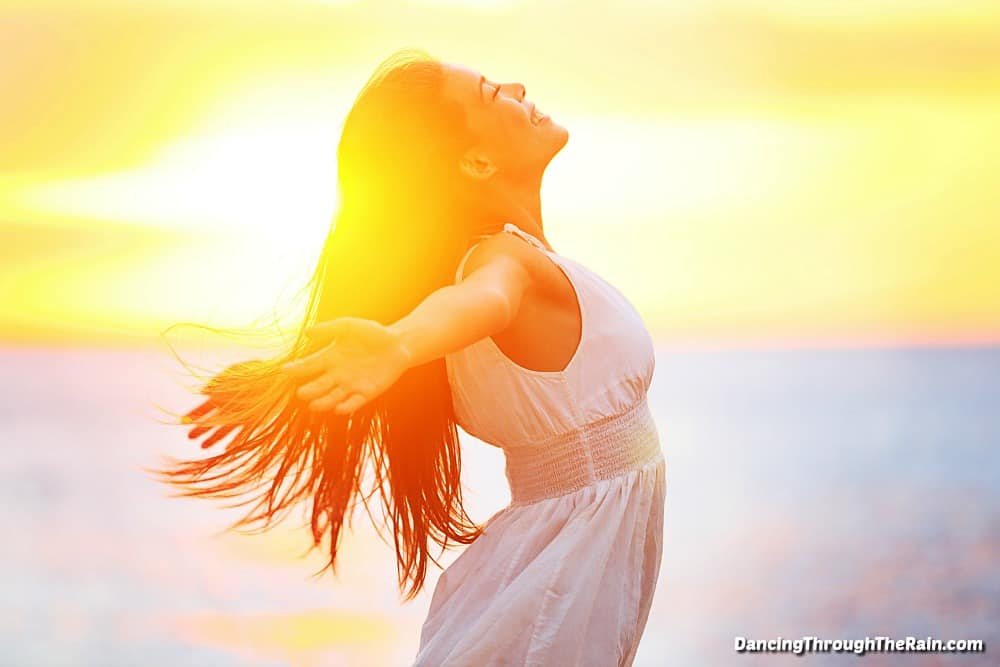 A woman standing in the sun with her arms open wide