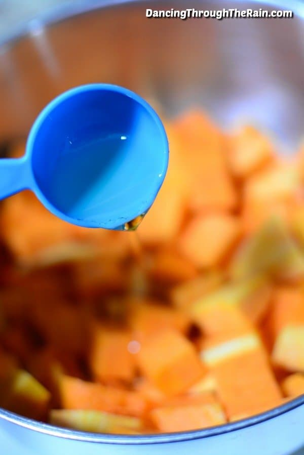Coconut oil being poured into a bowl with butternut squash cubes in it