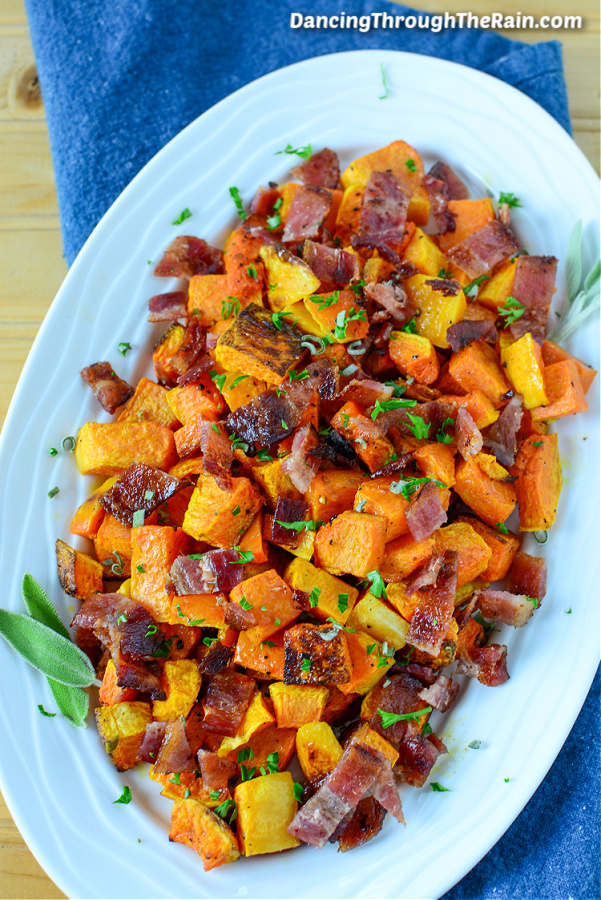 Roasted Butternut Squash and Bacon on a white serving platter on a blue tablecloth