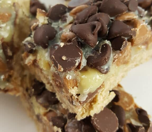 A pile of Seven Layer Cookie Bars on a white plate with a blue and white tablecloth underneath