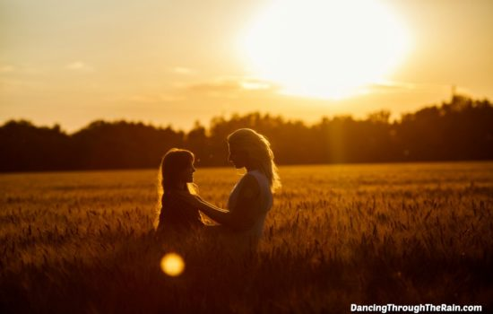 A woman talking to a child in a field at sunset