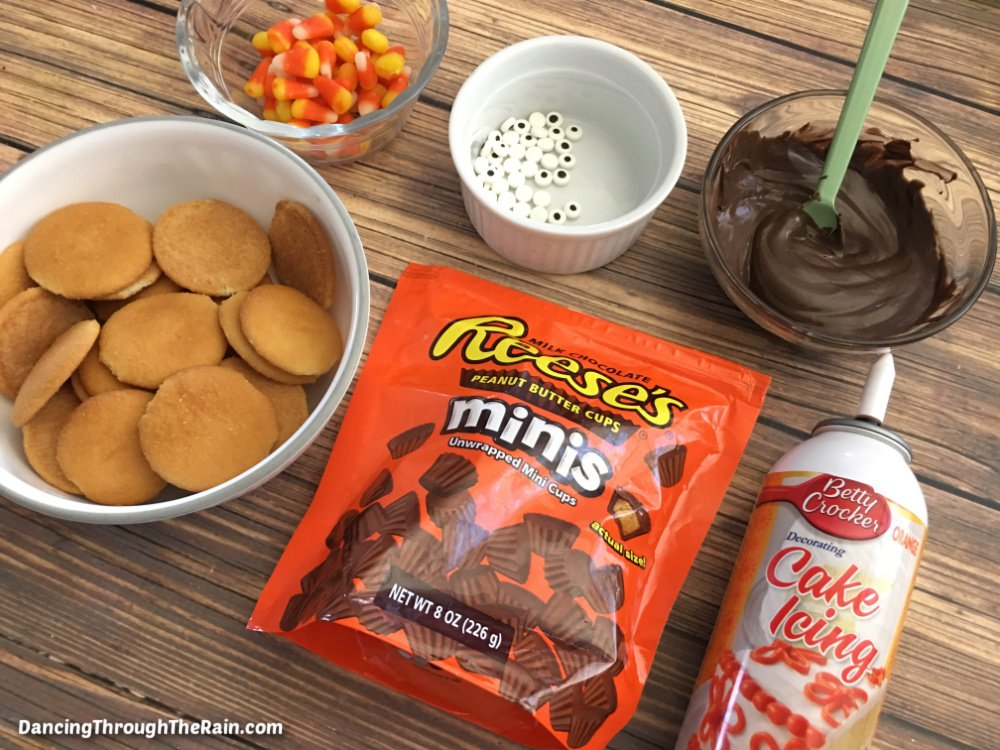 A bag of Reese's Minis, a white bowl of Nilla Wafers, a can of orange frosting, a clear bowl of brown frosting, a white bowl of candy eyes, and a clear bowl of candy corn on a wooden table