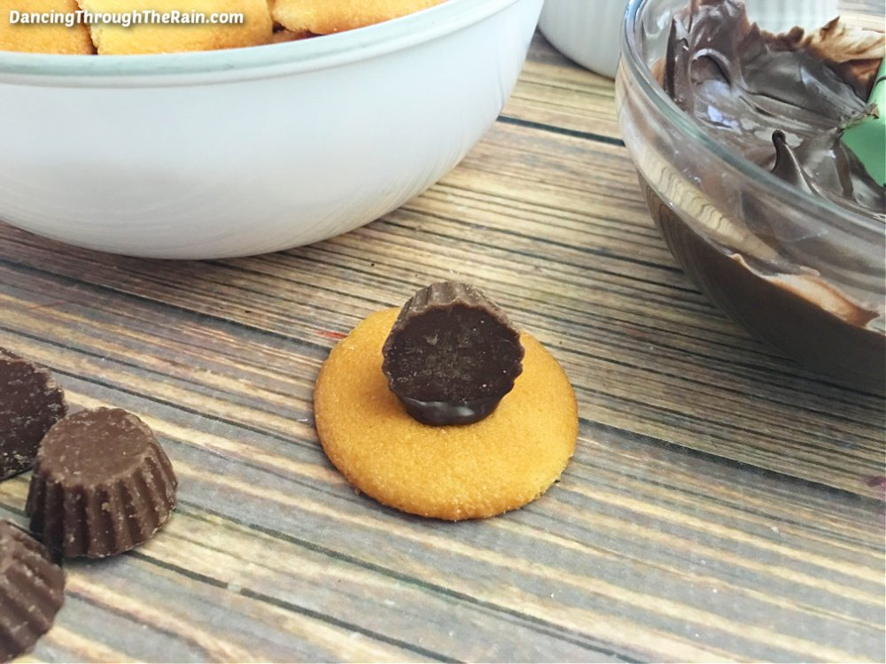 A white bowl of Nilla Wafers next to a clear bowl of melted chocolate candy melts next to a Nilla Wafer with a Reese's cup attached to a Nilla Wafer on a wooden table