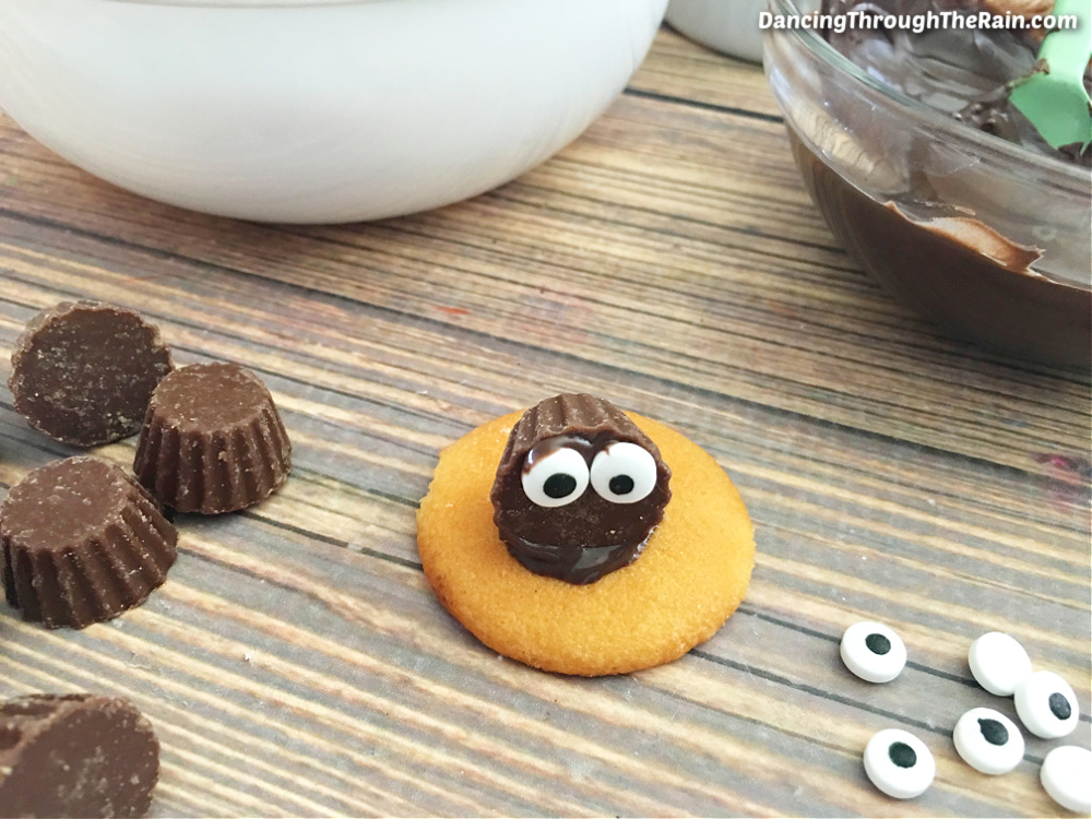 Nilla wafer with a Reese's cup on top and two candy eyes affixed to the front next to more candy eyes and more Reese's cups on a wooden table