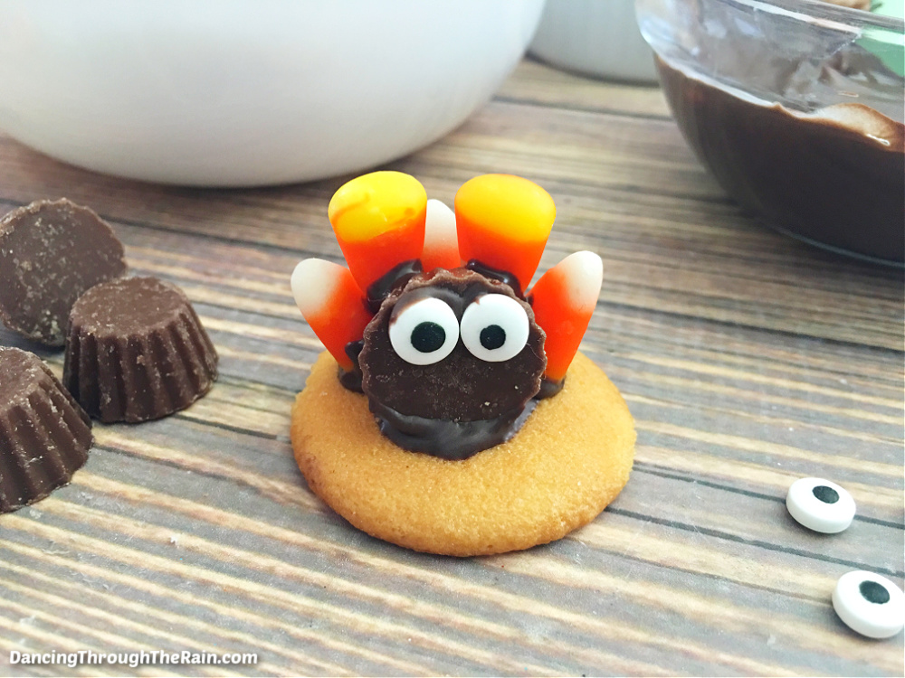 A Nilla Wafer with a Reese's cup on top with candy eyes affixed to the front and candy corn on the back on a wooden table next to more Reese's cups and candy eyes