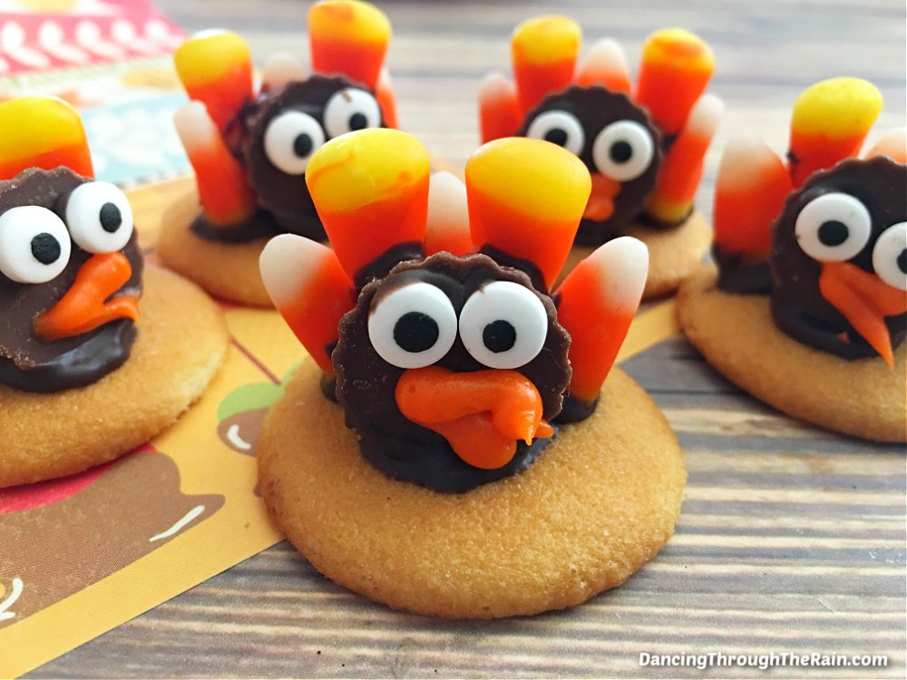 Five Candy Corn Turkey Cookies on a wooden table
