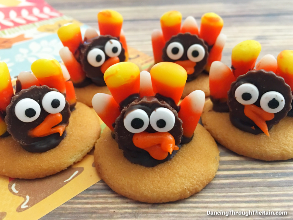 Five No-Bake Candy Corn Turkey Cookies on a wooden table